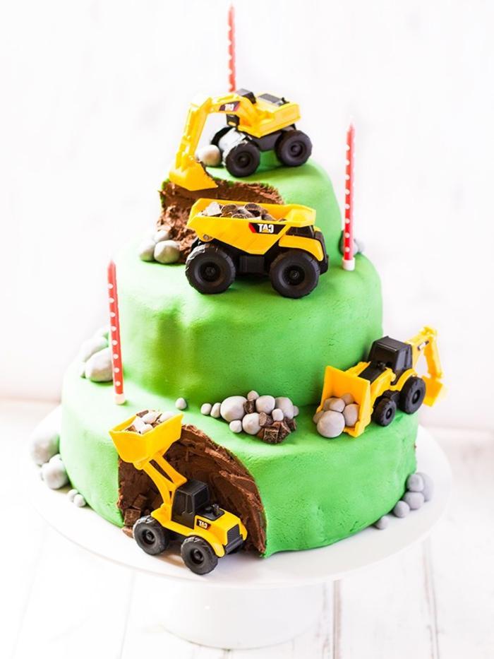 joli gateau d'anniversaire chantier de construction à trois étages recouvert de pâte à sucre vert et décoré de jouets pelleteuses