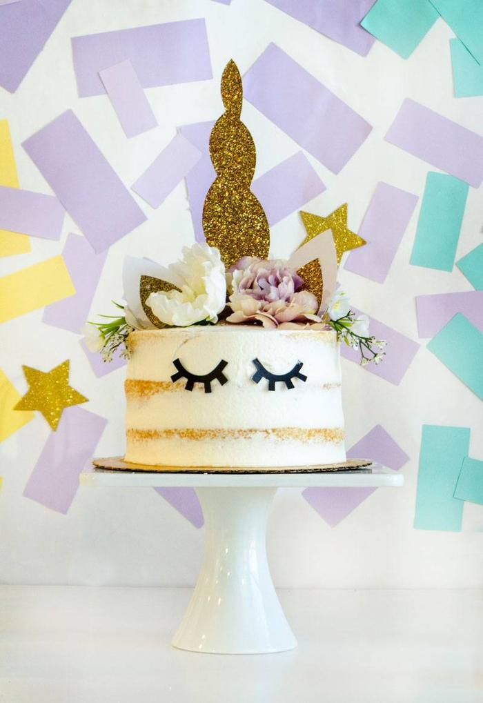 joli gateau licorne façon naked cake décoré avec des accessoires licorne et un mur de confettis en arrière-plan