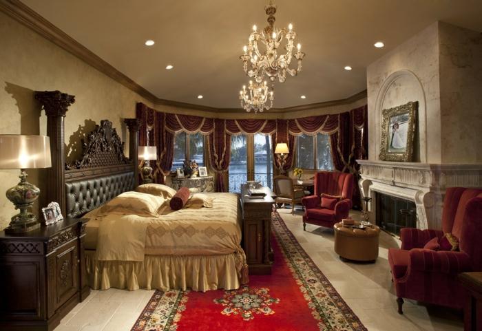 chambre style gypsy, lit beige, plafonnies somptueux, cheminée, fauteuils oranges, tête de lit en cuir