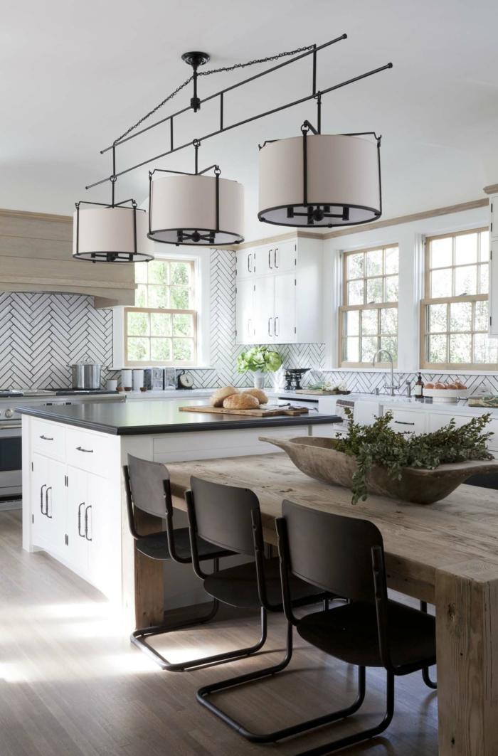 cuisine blanche et bois, chaises noires, îlot carré, plusieurs fenêtres et un décor lumineux