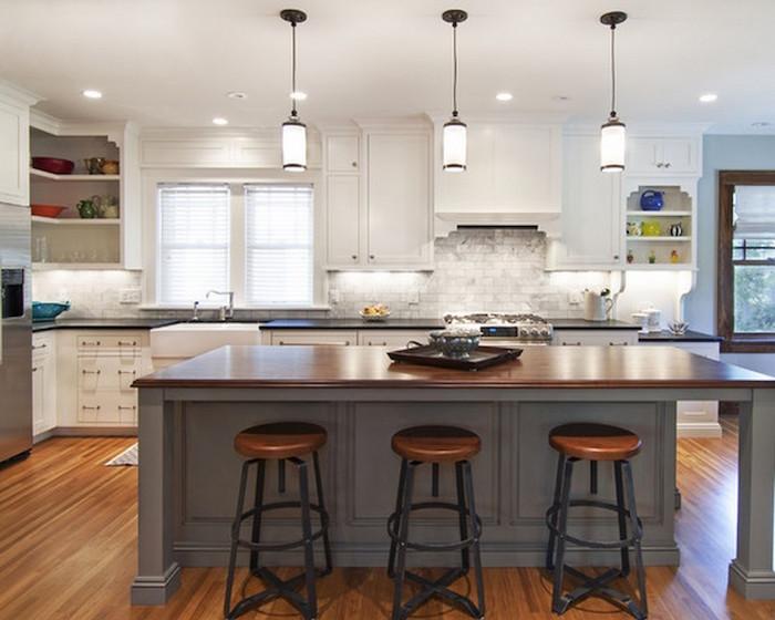 photo de cuisine blanche et grise sur sol en bois et ilot avec tabourets de bar