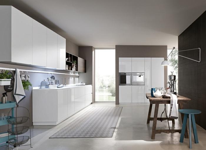 cuisine blanche équipée, table en bois brut, tabouret peint bleu, placards suspendus, tapis gris rectangulaire