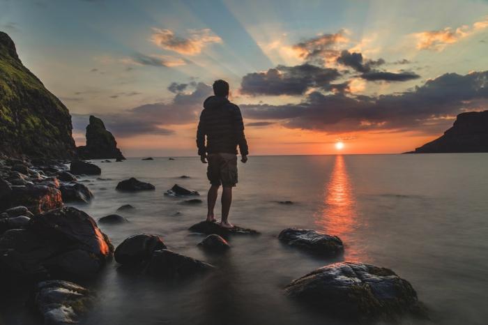 au bord de la mer, coucher de soleil, soleil rouge-orangé, eaux grisâtres, grands cailloux noirs, ciel aux rayons qui se filtrent parmi les nuages