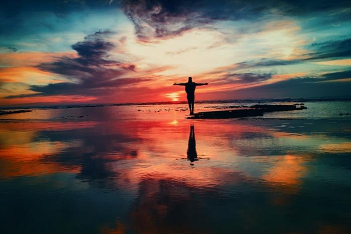 image de solitude, un homme sur la plage les bras levés vers les cieux, ciel en rose, bleu, orange et rouge, eaux immobiles comme un miroir