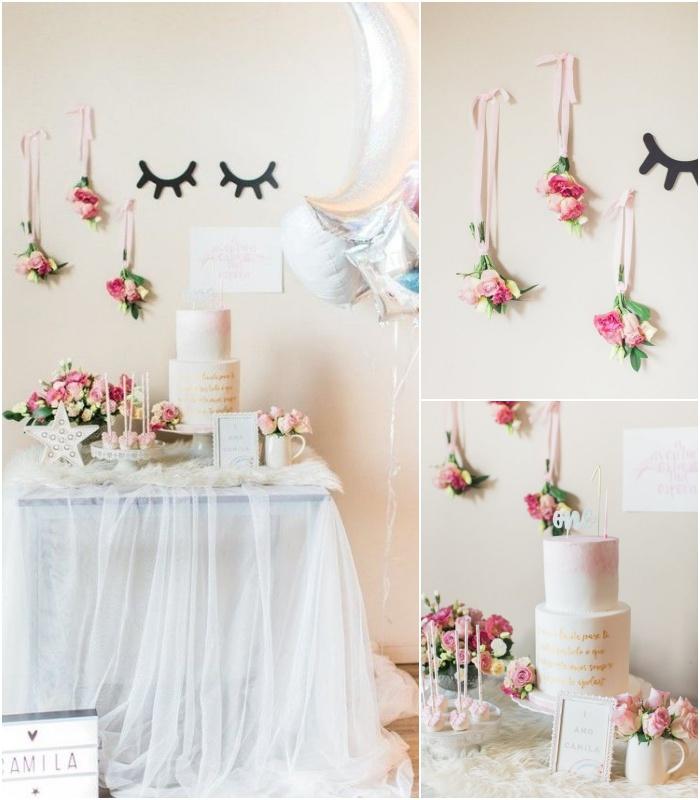 déco douce et aérienne d'un buffet d'anniversaire licorne avec une jupe de table en tulle, des bouquets de fleurs suspendus et des ballons aluminium argentés