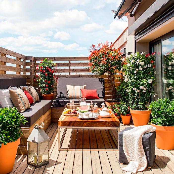 photo de terrasse fleurie avec pots de fleurs et jardinieres oranges, barriere en bois pour balcon contre vis a vis