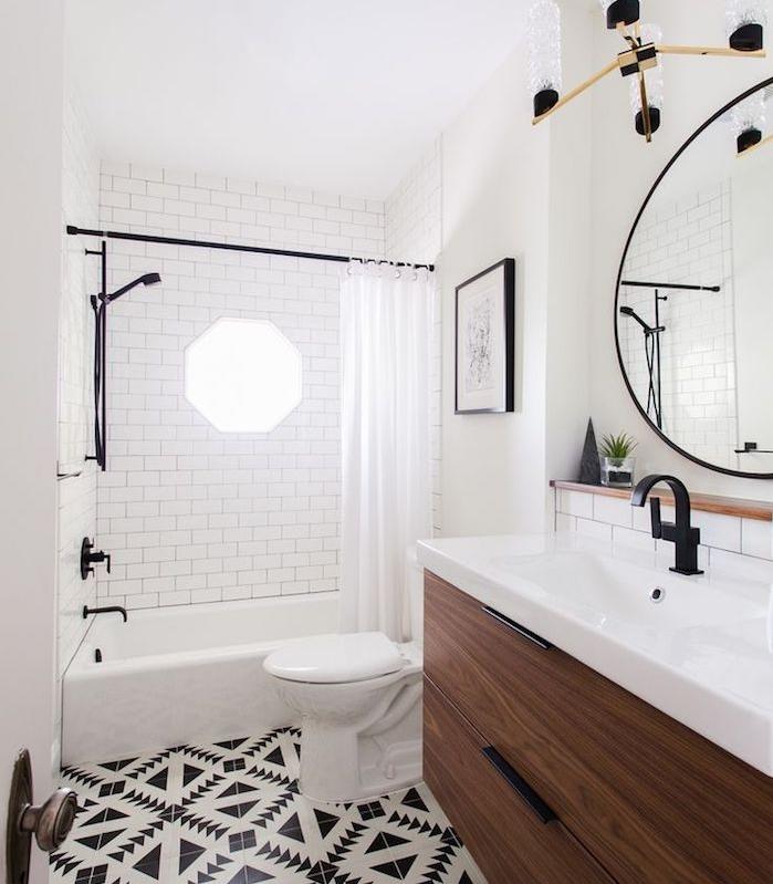 meuble petite salle de bain en bois avec lavabo blanc, grand miroir rond, baignoire avec rideau de douche, carrelage sol noir et blanc