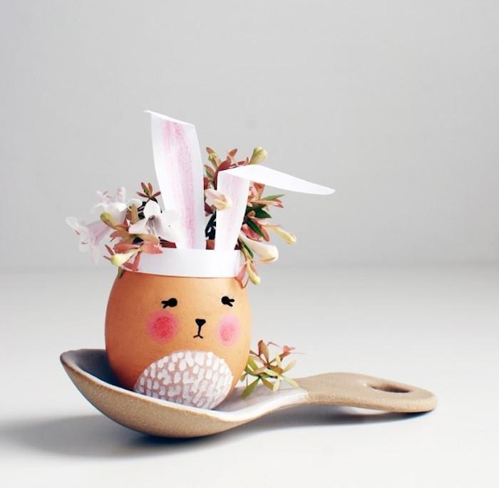 activité de paques avec une coquille d oeuf petit vase de fleur ,motif lapin de paques avec oreilles en papier et bouquet de fleurs à l intérieur