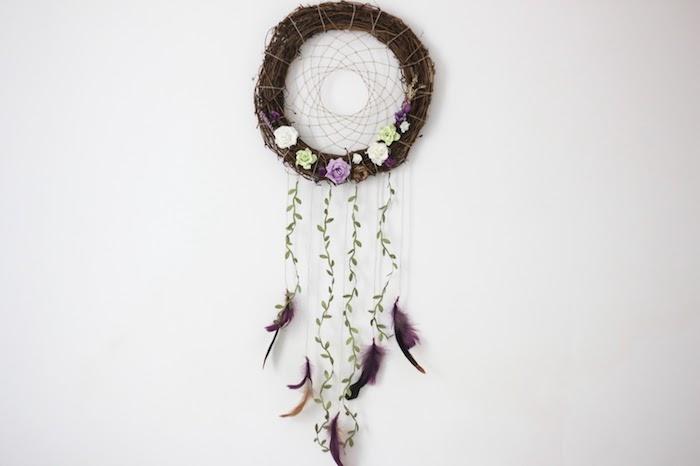 résultat final capteur de rêve en nids de branches, décoré de petites fleurs, plumes et branche avec feuilles vertes
