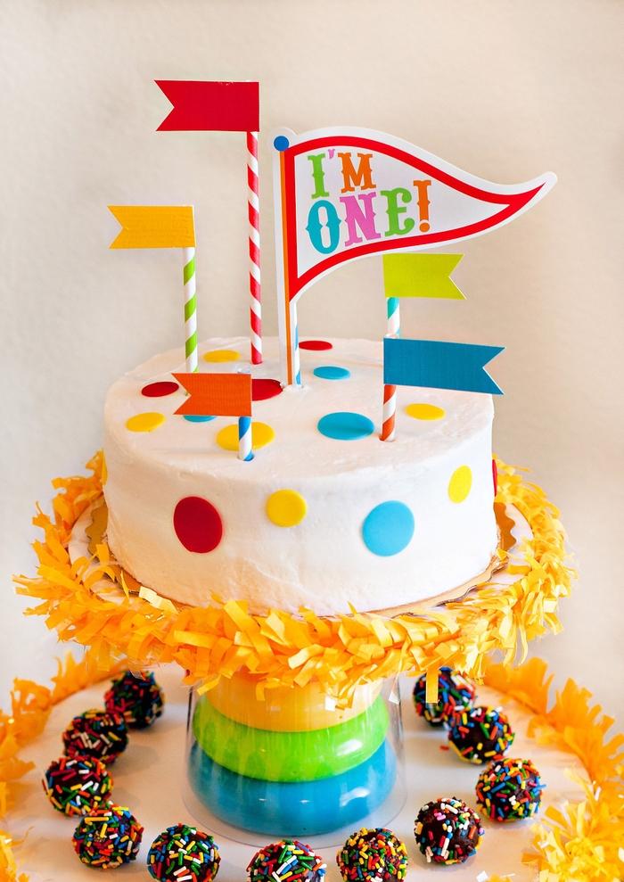 idée pour un gateau anniversaire 1 an facile à décorer soi-même, au glaçage blanc décoré de ronds en pâte à sucre coloré, pailles et fanions