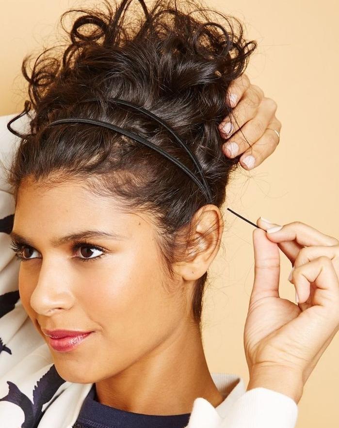 chignon haut décoiffé et bouclé accessoirisé d une serre tête, coiffure cheveux frisés originale avec volume