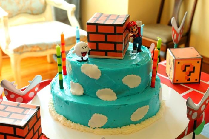 un gateau d'anniversaire à deux étages sur thème super mario recouvert de glaçage bleu décoré de nuages en pâte à sucre et de figurines super mario