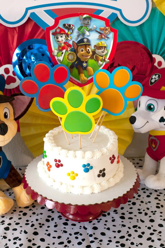 gâteau d'anniversaire garçon sur le thème la pat patrouille au glaçage blanc décoré de cake toppers pattes en papier
