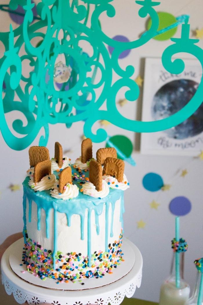 gateau d'anniversaire personnalisé au glaçage bleu pastel coulant décoré de biscuits et de confettis colorés