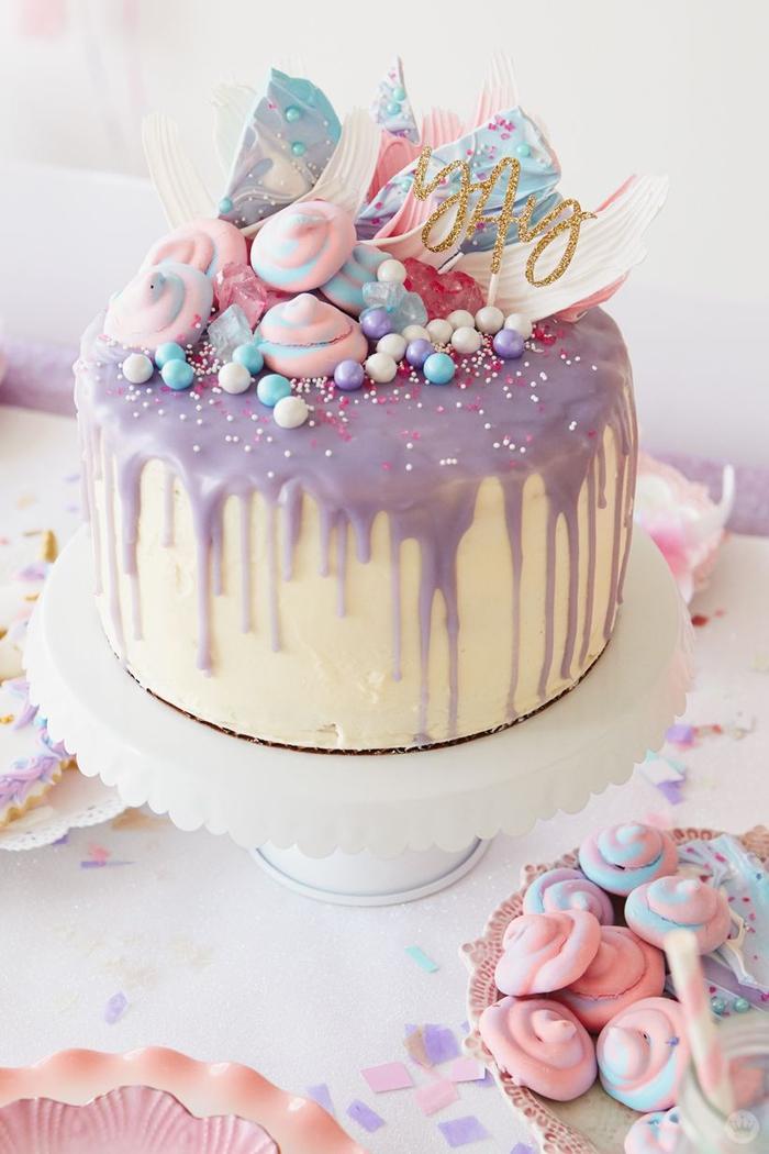 joli gateau licorne au glaçage coulant rose lavande avec une décoration de meringues licorne et des perles de sucre colorées