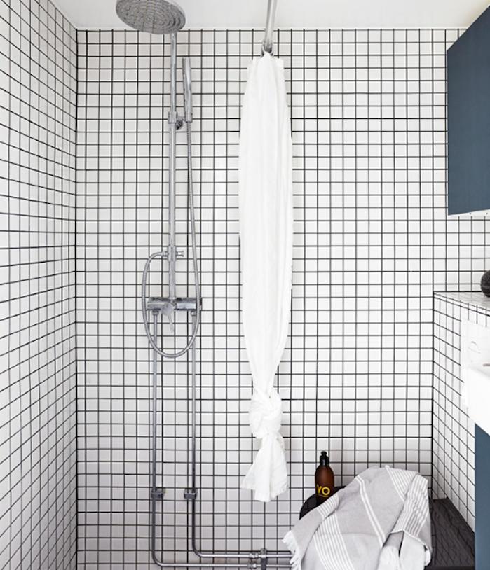 modele de petite salle de bain design avec carrelage mural blanc, douche argent, et meubles de rangement bleus