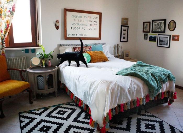 deco pour chambre bohème chic avec une galerie murale de cadres dépareillés et un dessus de lit personnalisé avec des pompons colorés