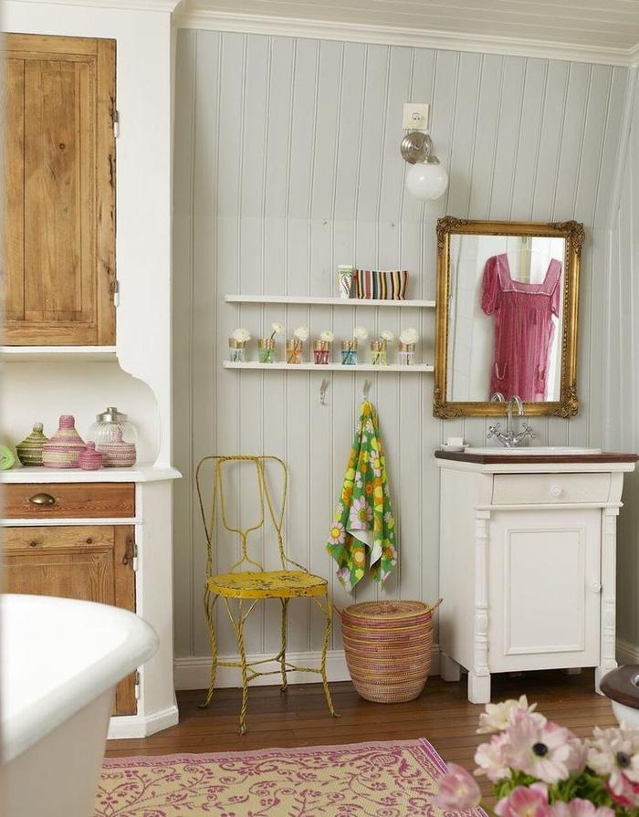 salle de bain ancienne au lambris de bois et aux touches colorées avec un coin vasque vintage