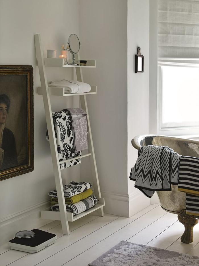 une baignoire sur pied et une étagère échelle pour une ambiance relaxante dans la salle de bain ancienne