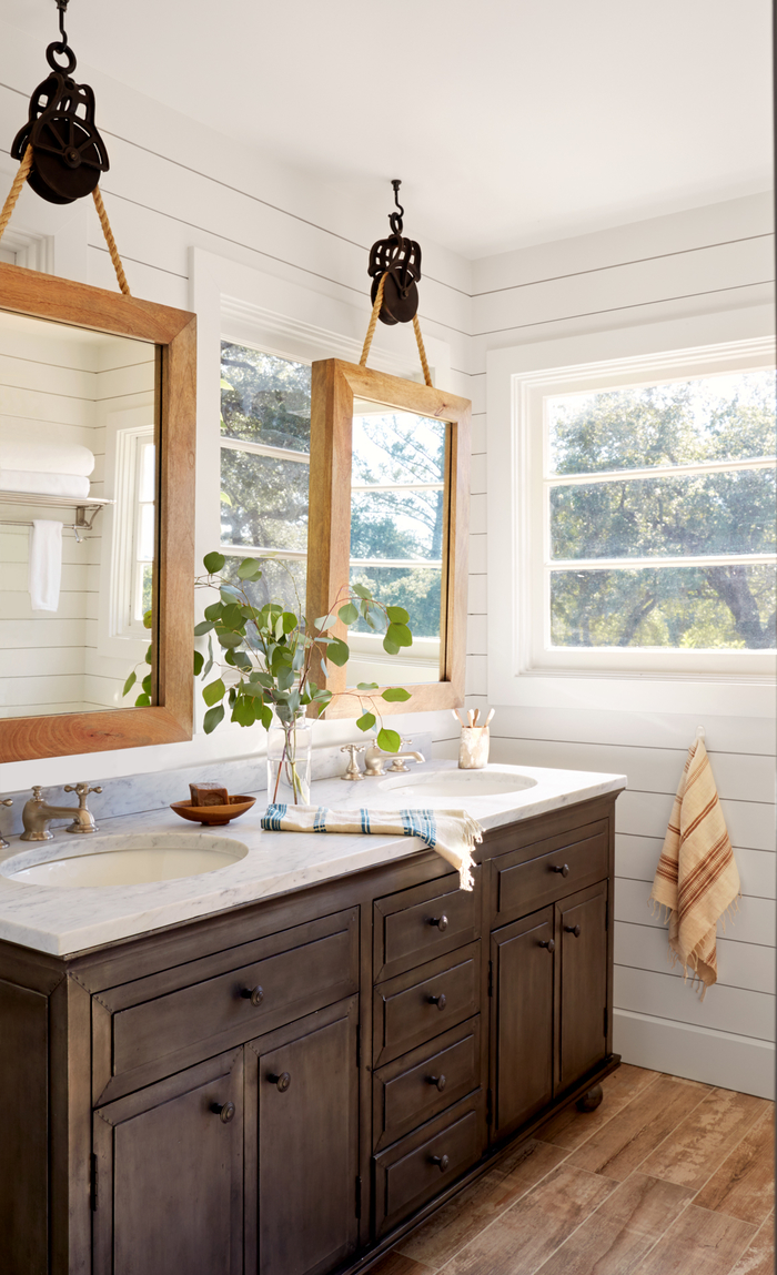 une commode salle de bain récup à nombreux tiroirs pour un espace de rangement maximal en contraste avec les miroirs industriels suspendus dessus