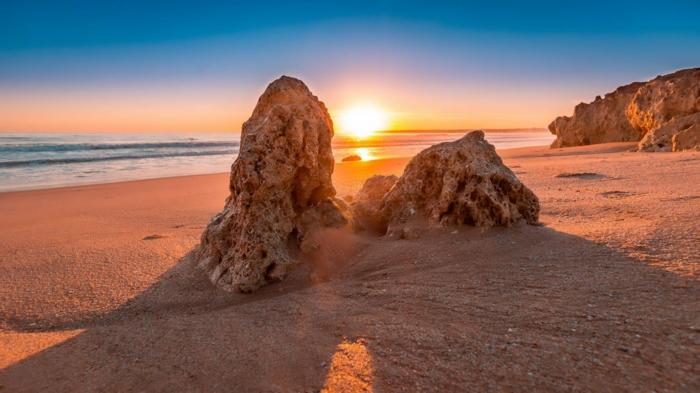dunes de sable, roches en pierre poreuse, ciel sans nuages, soleil couchant aux nuances jaunes, sable beige, paysage paradisiaque