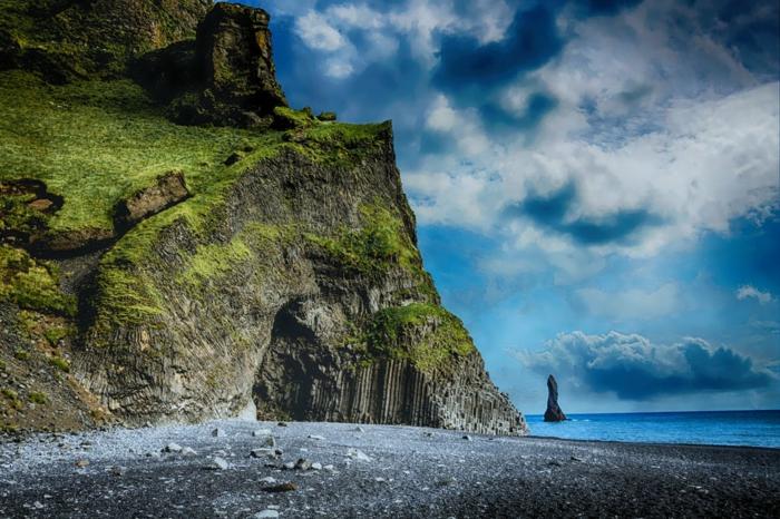 lagon entouré de roches recouvertes de verdures, paysage paradisiaque, cailloux blancs sur la plage, rocher noir au milieu de la mer