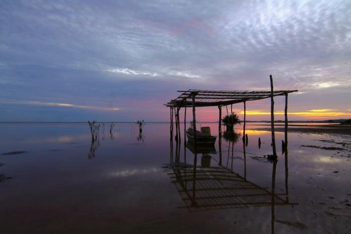 fond ecran paysage, barque dans un petit port improvisé, avec une construction faite main, ciel nuages bleus et roses, eaux immobiles