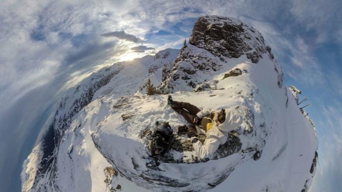 paysage paradisiaque, montagne en neige, vue d'en haut, effet de tourbillon, ciel bleu avec des nuages blancs, sommet rocheux