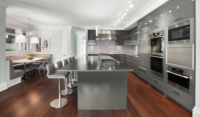 grande cuisine pro grise avec grand ilot central, cuisine moderne couleur gris béton sur sol en bois foncé