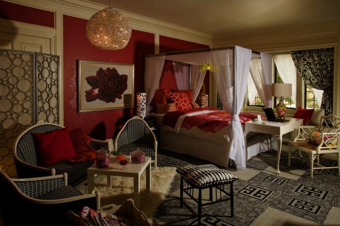 mur et couettes couleur bordeau, chaises et table basse élégante, lit avec rideaux