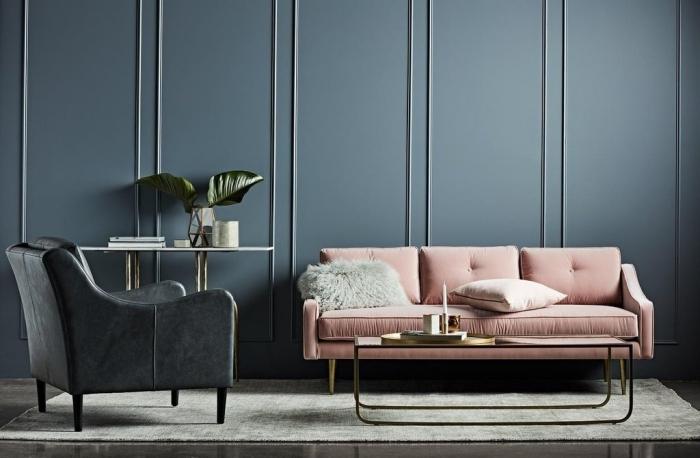 déco de salon foncé avec table à design métallique combinée avec canapé rose poudré et fauteuil de cuir noir sur tapis gris clair