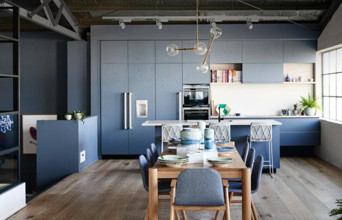bois et bleu dans la cuisine, table à manger en bois, lampes molécules, sol de bois