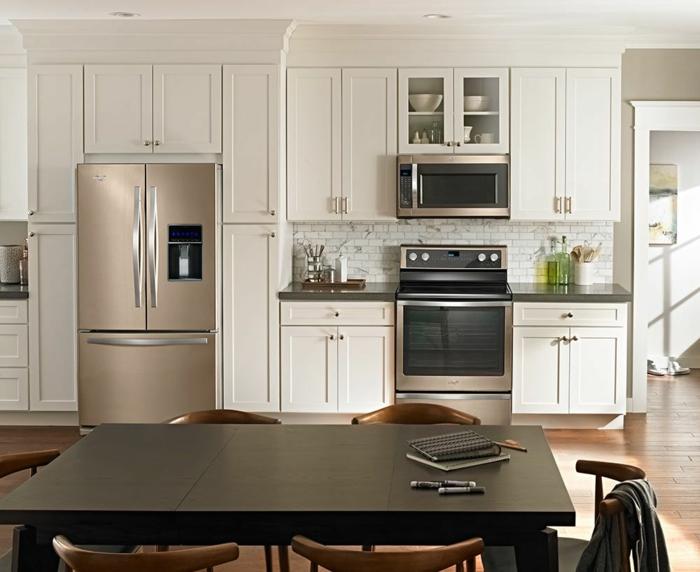 grande table noire, chaises en bois, frigo moderne, cuisine incorporée, mur avec rangement intégré