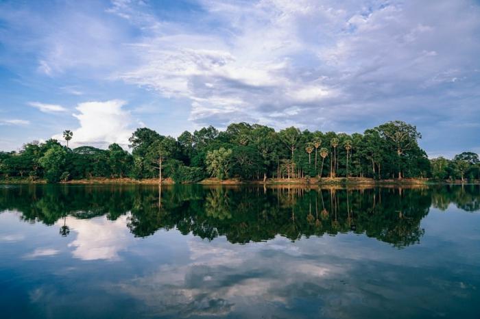 fond ecran paysage, beau paysage, iles paradisiaques, paysage mer, palmes et végétation tropicale, nuages blancs qui reflètent dans les eaux tranquilles