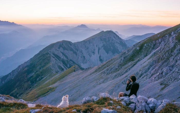 une photographe assise aux bords d'une roche, montagnes avec des roches blanches, ciel en nuances oranges et bleues, chien blanc