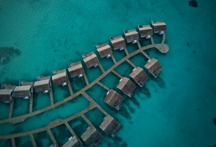 maisons dans l'eau avec un réseau de petits chemins entre elles, océan vert, lagune, ambiance de vacances, toits des maisons vus d'en haut