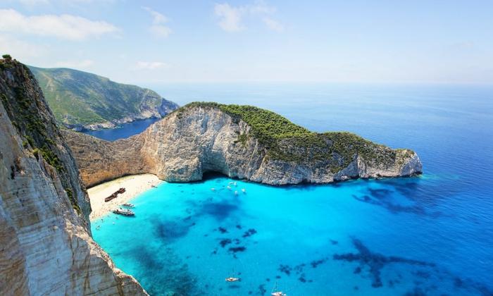 fond ecran paysage, eaux bleues, roches argileuses, ciel nuageux, petite plage de sable fin beige, panorama magnifique, photo prise d'en haut d'une roche