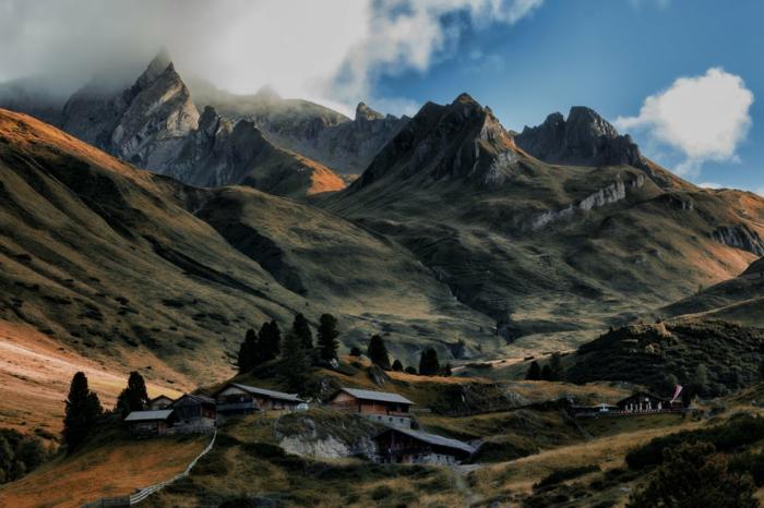 montagne rocheuse avec des sommets gris, destination paradisiaque, des maisons montagnardes au loin dans la plaine, paysage paradisiaque