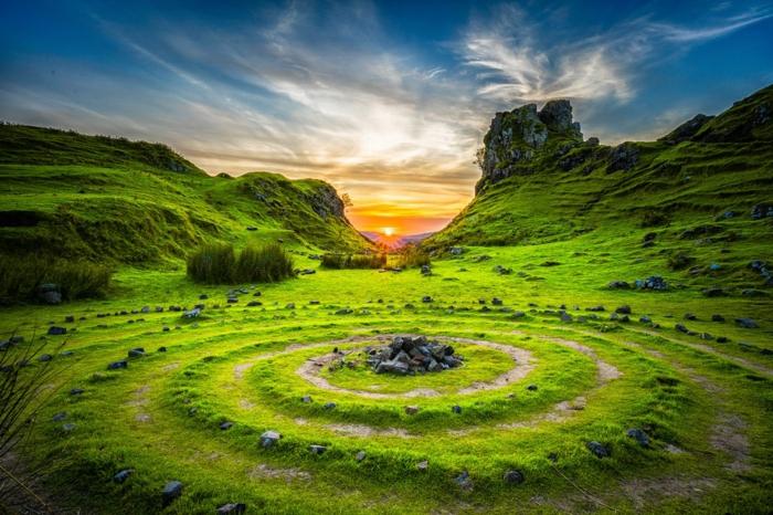 spirales vertes avec des pierres noires, paysage paradisiaque, soleil jaune qui se couche, ciel bleu avec des nuages-voiles, paysage de reve
