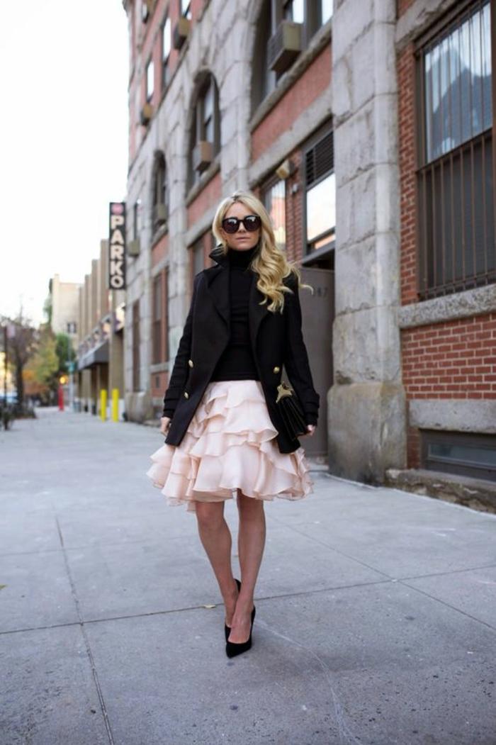 look en veste noire aux boutons dorés et jupe en rose délicat, avec des nombreux volants, tenue de fête femme, chaussures noires talons aiguilles pointues