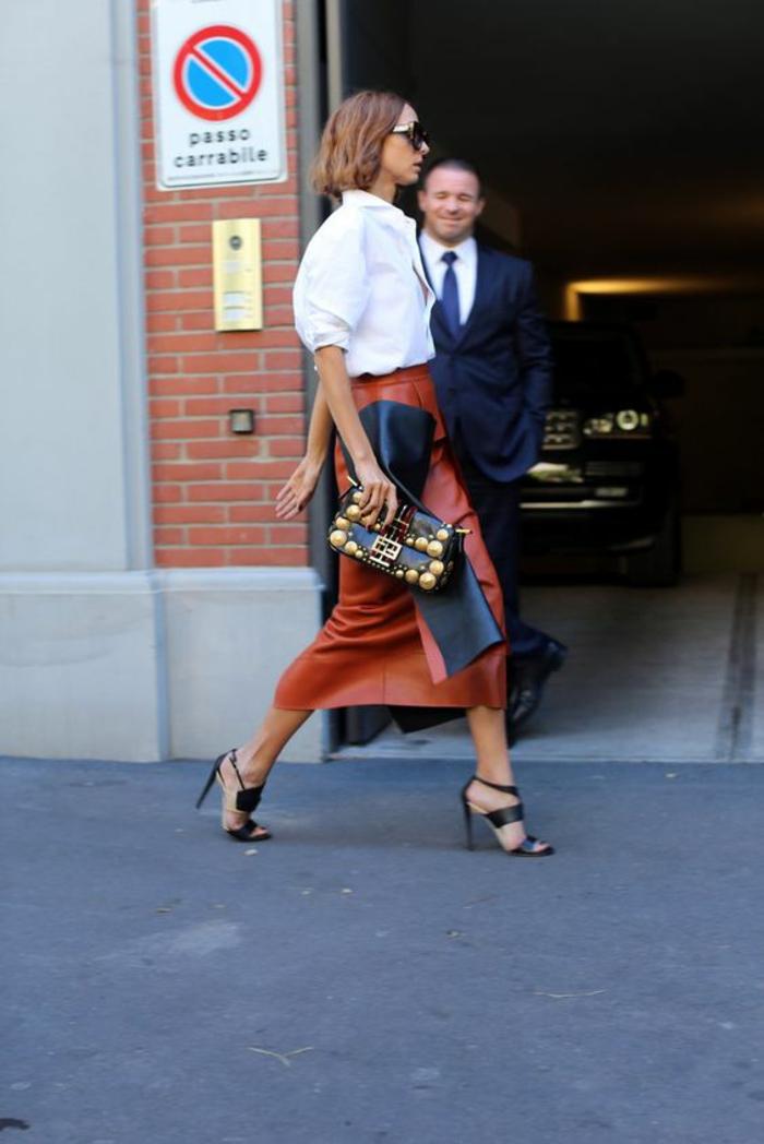 jupe longue aux chevilles imitation cuir en couleur brique, tenue chic, bien habillée, sandales noirs, chemise blanche manches 3-4 bouffantes, sac noir avec des ornements métalliques imitation or
