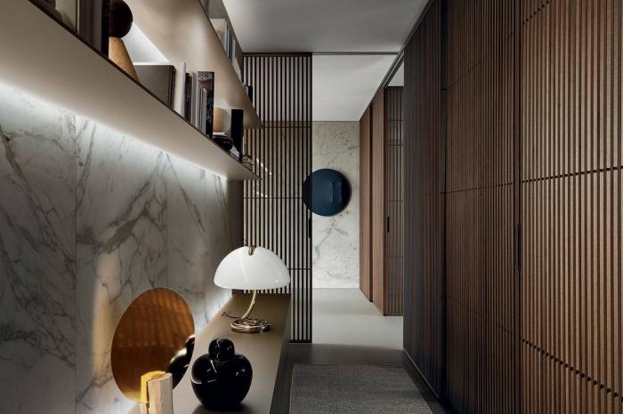 comment aménager un couloir en couleurs foncées avec revêtement mural à design marbre et pan en bois foncé