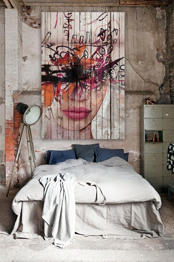 chambre à coucher moderne aménagée en style industriel avec une lampe sur pied design brut et une déco de pan mur en tapisserie art