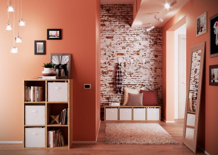 deco hall entrée aux murs oranges avec pan de briques rouges et blanches, modèle de suspension lumineuse avec cordes et ampoules en verre