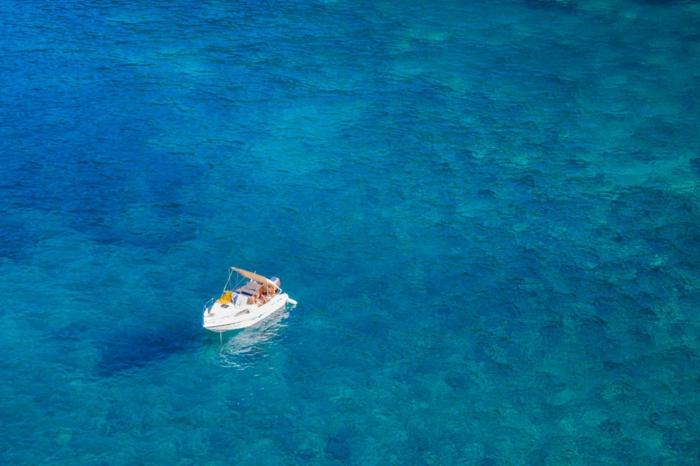 le grand bleu, barque touristique blanche dans les eaux bleues transparentes, au milieu de l'océan, iles paradisiaques,, paysage paradisiaque