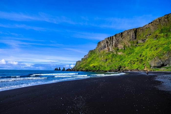 sable noir, roches marrons a l'horizon, ondes blanches sur la mer bleue, roches recouvertes de vert, nuages blancs