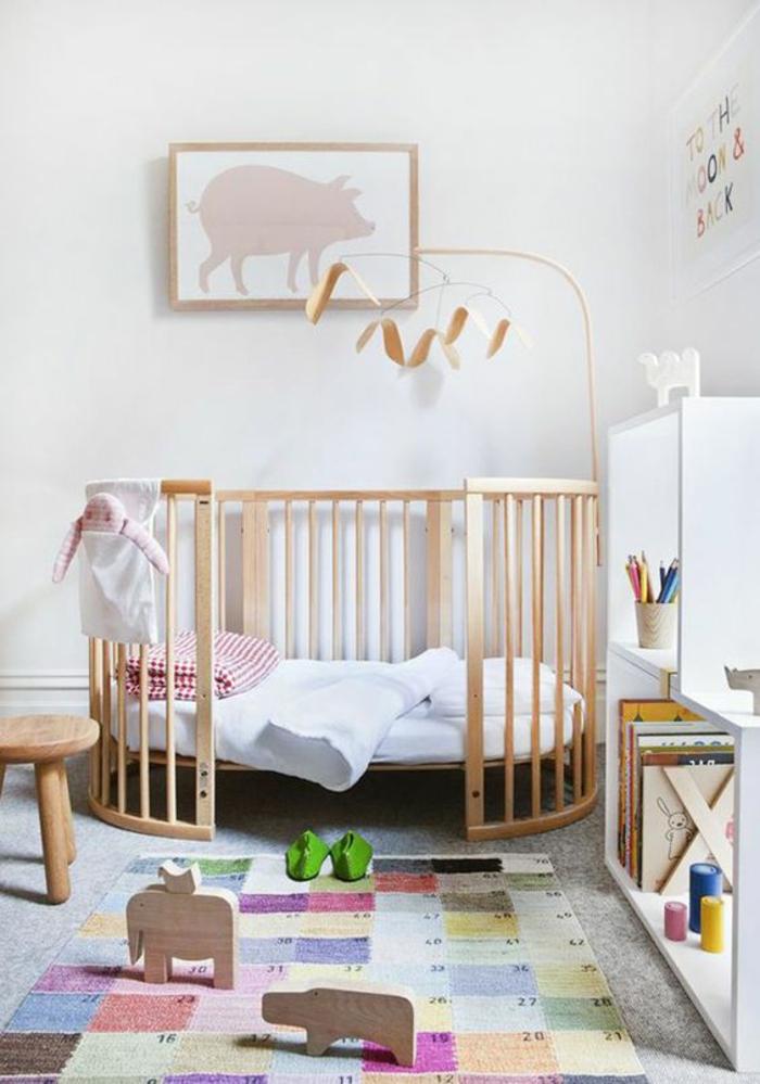 chambre rose et gris, lit rond avec des barreaux, tapis type patchwork coloré, tableau chambre bébé avec un cochon rose, tabouret rond avec trois pieds en bois clair
