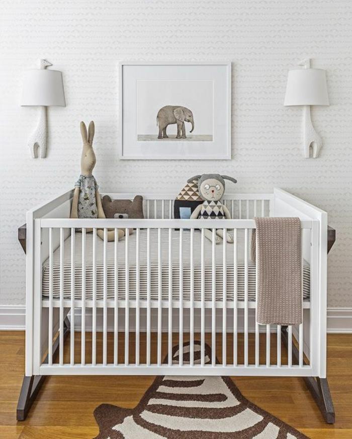 lit bébé blanc en bois, tapis en forme de peau de zèbre, deux luminaires appliques avec des abat-jours blancs en forme de girafes, parquet en jaune, tableau avec éléphant gris au cadre blanc