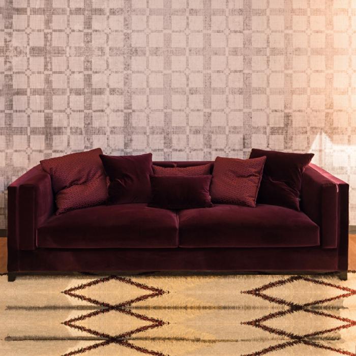canapé deux places lie de vin couleur, tapis beige à motifs géométriques, papier peint géométrique