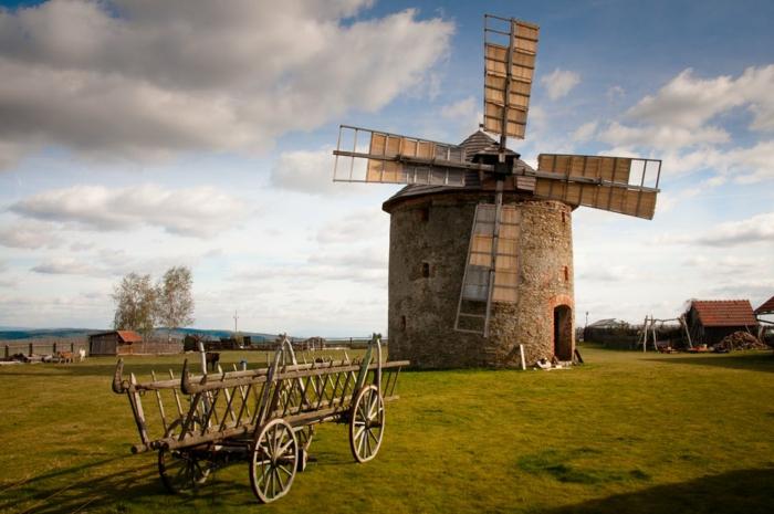 iles paradisiaques, moulin a vent, paysage idyllique champêtre, ciel bleu et nuages blancs, chariot en bois gris a quatre roues